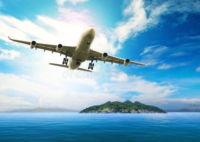 Avião comercial que voa sobre o oceano e a ilha azuis bonitos em p foto de stock