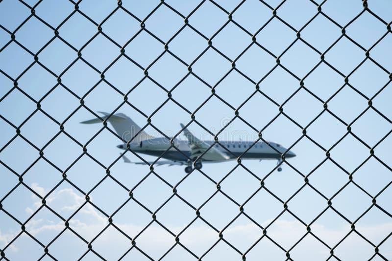 Avião de aterrissagem atrás da cerca de fio da malha no aeroporto imagem de stock royalty free
