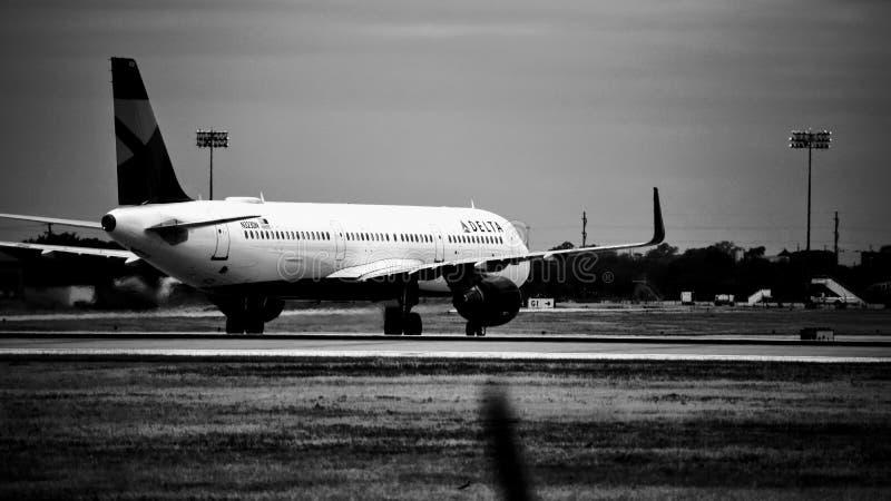 Avião de Delta Airlines na pista de decolagem preto e branco imagens de stock