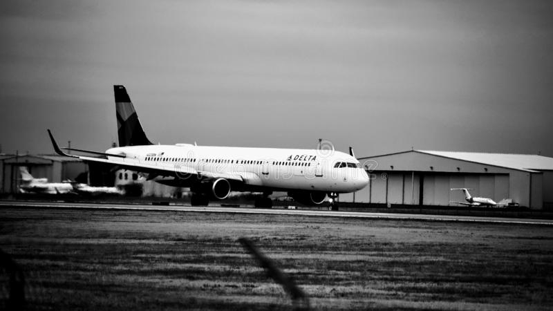 Avião de Delta Airlines na pista de decolagem preto e branco foto de stock royalty free