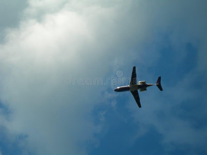 Avião de encontro ao céu nebuloso fotografia de stock