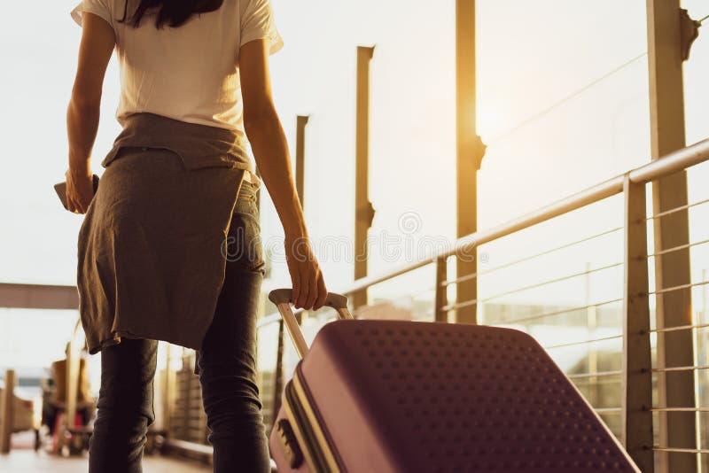 Avião de espera do viajante da mulher após ter registrado o voo do bilhete no aeroporto foto de stock
