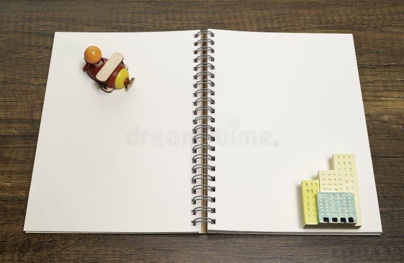 Avião de madeira vermelho no caderno branco vazio com o brinquedo de construção cerâmico imagem de stock royalty free