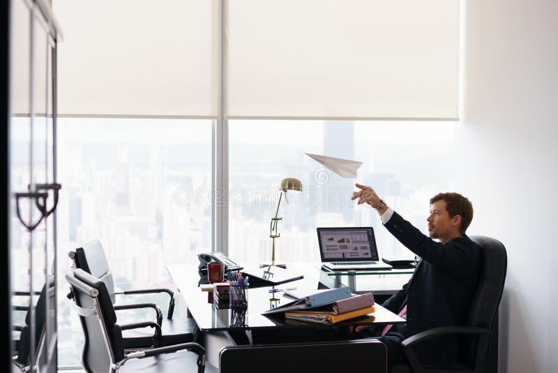 Avião de papel de jogo da fantasia bem sucedida do trabalhador de escritório do homem imagem de stock