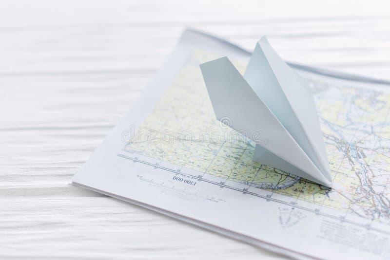 Avião de papel, em um mapa em um fundo de madeira fotografia de stock royalty free