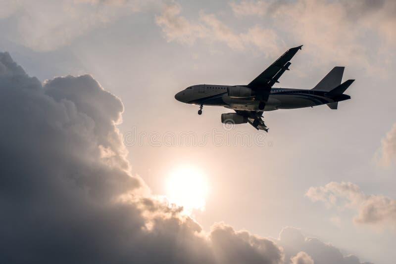 Avião do voo no céu com Sun e nuvens imagem de stock royalty free
