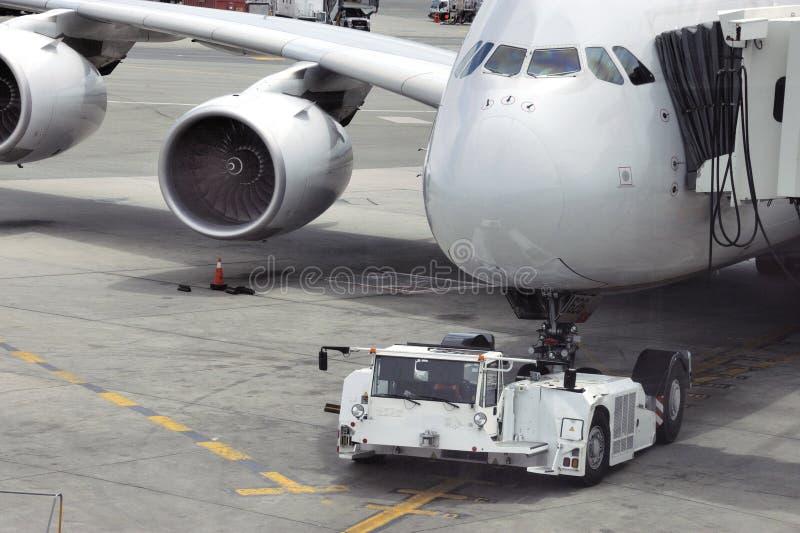 Avião em pista de aeroporto com trator de reboque imagens de stock