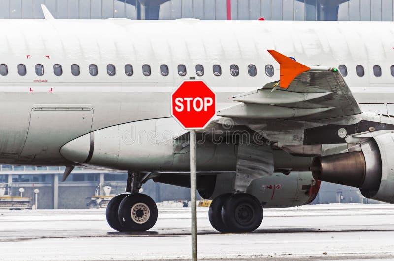 Avião em vigias e em asa do aeroporto, na frente delas sinal da parada imagem de stock royalty free
