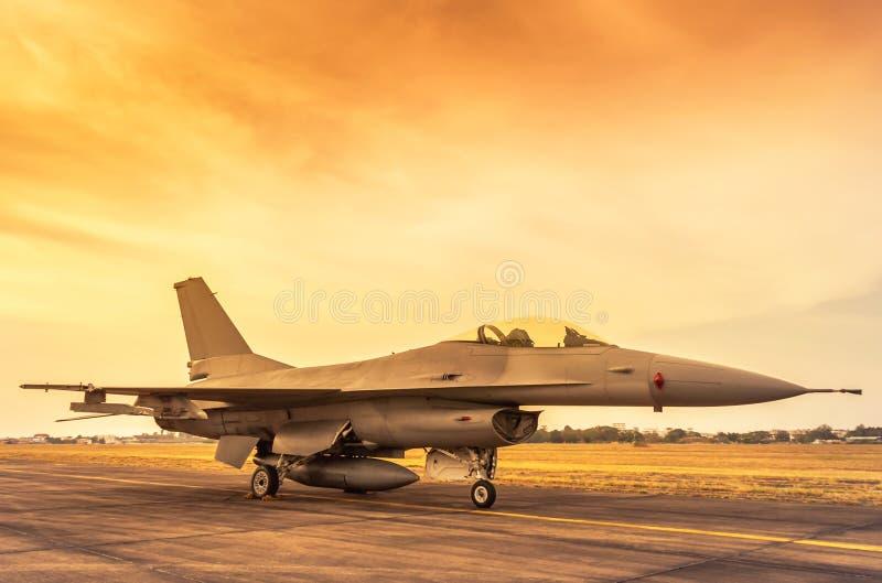 avião militar do avião de combate estacionado na pista de decolagem no por do sol imagem de stock royalty free