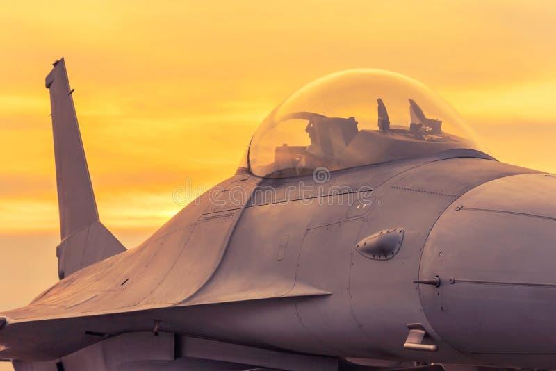 Avião militar do avião de combate estacionado na pista de decolagem no tempo do por do sol fotografia de stock