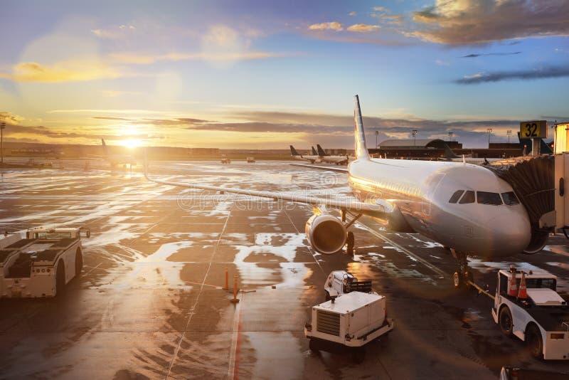 Avião na porta terminal no aeroporto internacional fotografia de stock