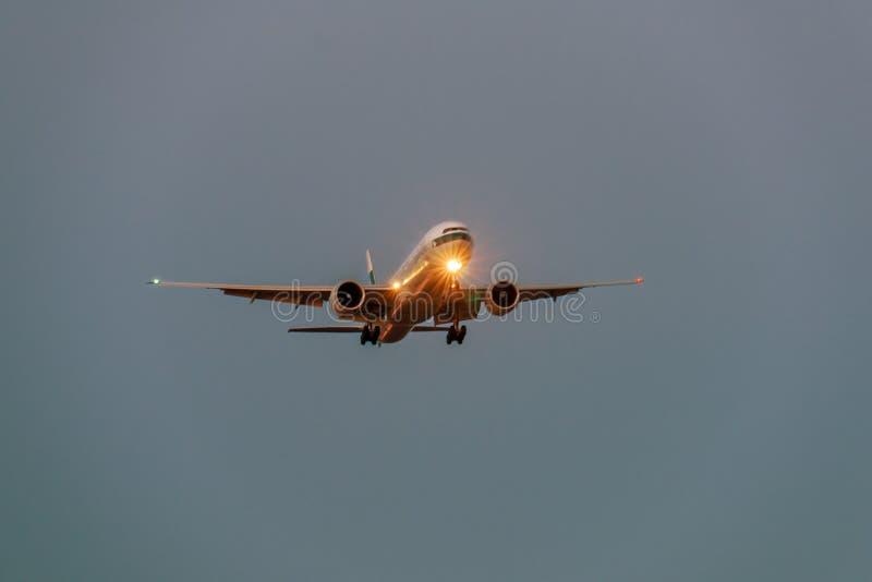 Avião no céu cinzento na noite com farol imagens de stock royalty free