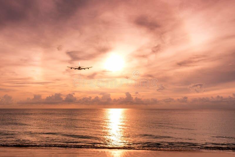 Avião que voa para formar arcos luz solar no mar na noite foto de stock
