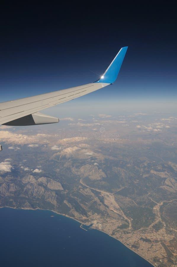 Avião sob montanhas e mar imagens de stock