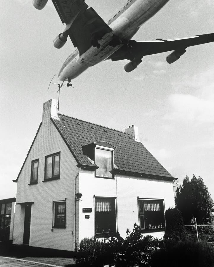 Avião sobre a casa fotografia de stock royalty free
