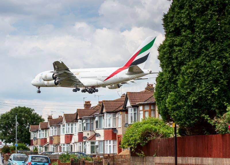 Avión de Airbus A380 de los emiratos que aterriza sobre casas imágenes de archivo libres de regalías