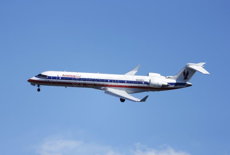 Avión de Eagle Bombardier CRJ-700 del americano en el cielo de Nueva York antes de aterrizar en el aeropuerto de Guardia del La fotos de archivo libres de regalías