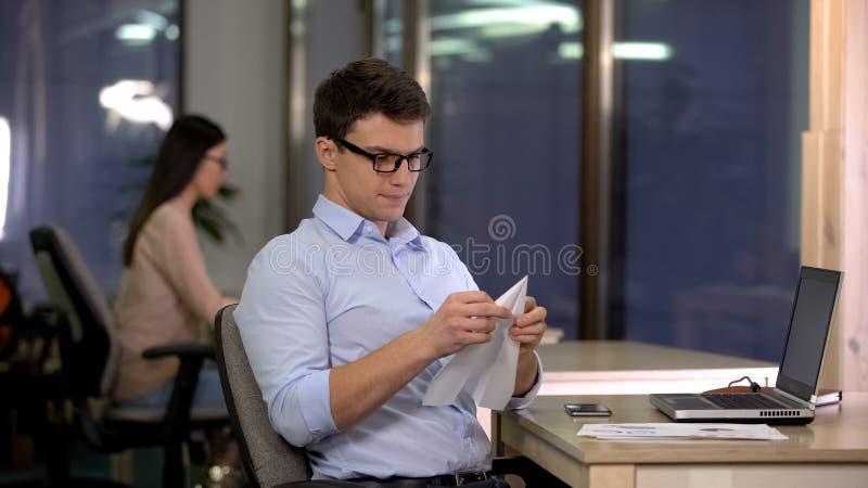 Avión de fabricación masculino juguetón del papel en la oficina, trabajo rutinario monótono cansado, rotura foto de archivo