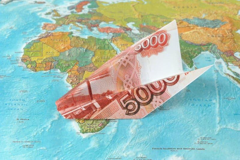 Avión de la papiroflexia hecho del dinero en el mapa fotos de archivo
