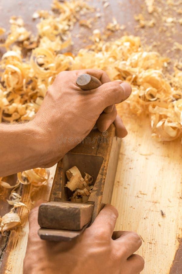 Avión de madera de la mano Primer de las manos del carpintero que afeitan con un avión en un taller de la carpintería foto de archivo libre de regalías