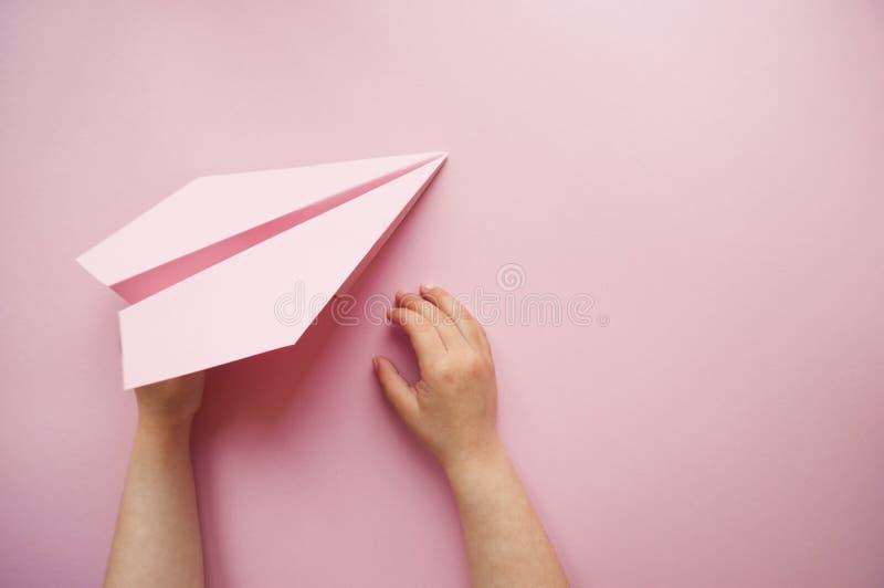 Avión de papel en manos del ` s del niño fotos de archivo