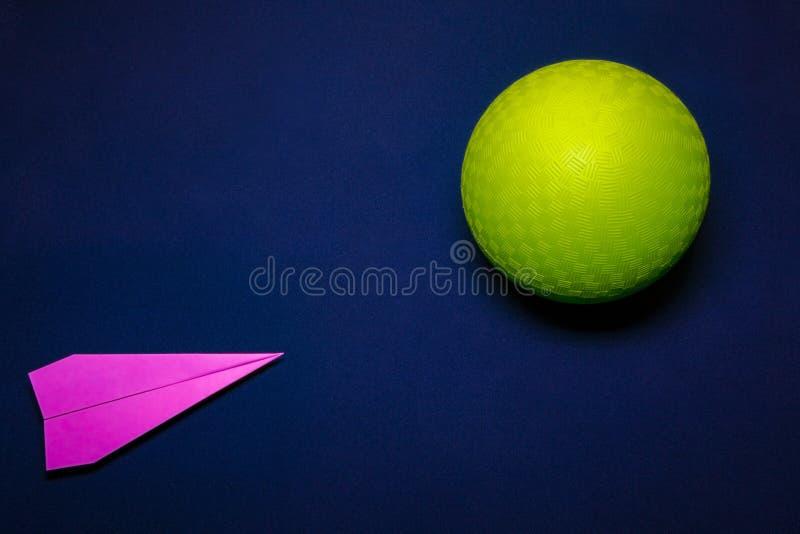 Avión de papel y bola verde en el fondo azul marino, concepto de la idea foto de archivo libre de regalías