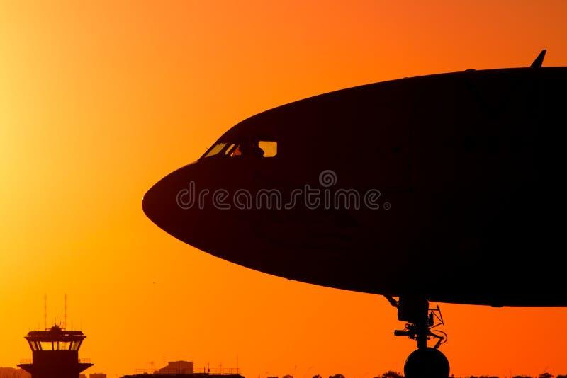 Avión de pasajeros del jet en la puesta del sol en silueta fotos de archivo