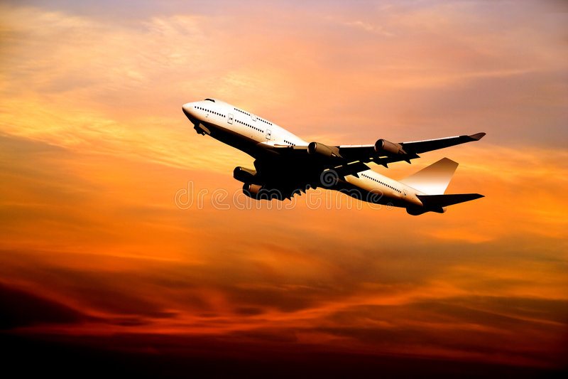 Avión de pasajeros que saca en la puesta del sol imagenes de archivo