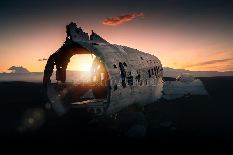 Avión estrellado Dakota en la playa negra en la puesta del sol imagen de archivo