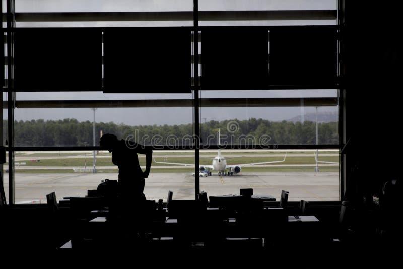 Avión que espera de la silueta de la mujer para en salón del aeropuerto fotografía de archivo
