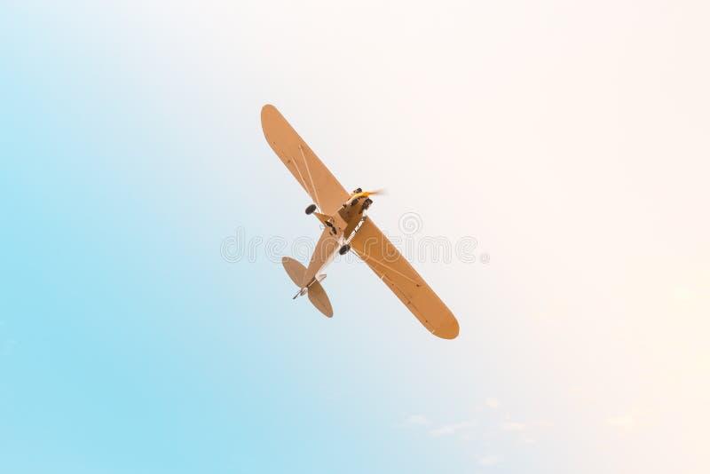 Avión retro con el vuelo del propulsor a través del cielo en colores en colores pastel rosados azules imagen de archivo libre de regalías
