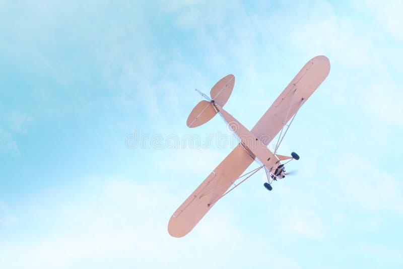 Avión retro con el vuelo del propulsor y zambullidas contra el cielo azul foto de archivo