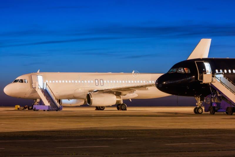 Aviões brancos e pretos do passageiro no avental do aeroporto no crepúsculo imagens de stock royalty free