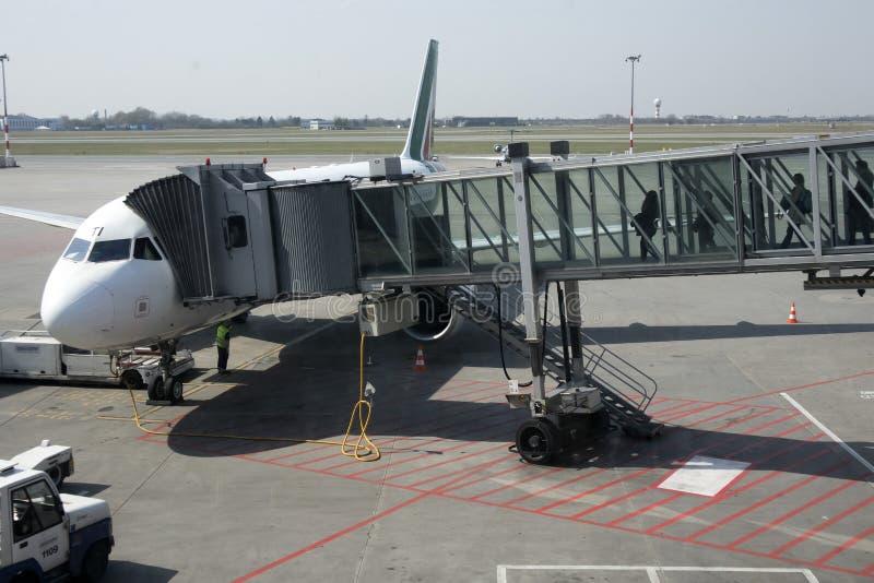 Aviões com o corredor/túnel da passagem que está sendo preparado para a partida de um aeroporto internacional - Passangers que em imagem de stock