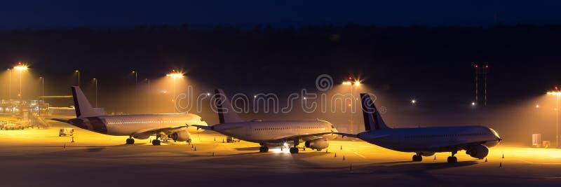 Aviões do passageiro que esperam em um aiport na noite imagem de stock