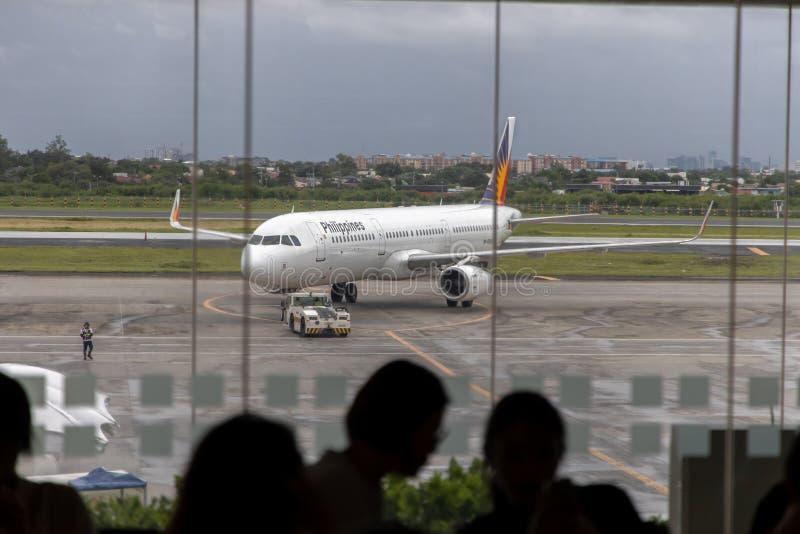 Aviões filipinos da linha aérea que preparam-se para embalar passageiros, Manila, Filipinas, o 18 de julho de 2019 imagens de stock