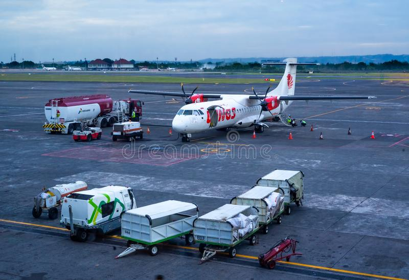 Avi?es g?meos da turbo?lice do ATR 72 do motor de Wing Airlines Being Fuel pelo caminh?o de petroleiro de Pertamina imagem de stock