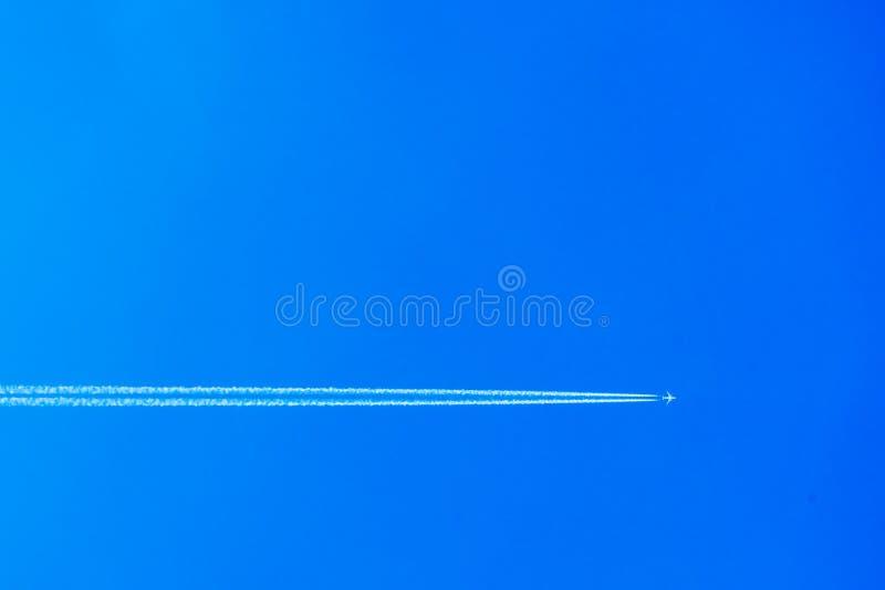 Avi?o com o contrail no c?u azul O conceito da liberdade, movendo-se para a frente Fundo do c?u foto de stock royalty free