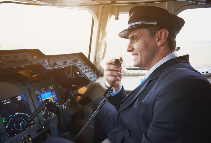 Aviador alegre que fala pelo transmissor portátil imagem de stock royalty free