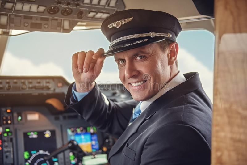 Aviador alegre que senta-se na cabina do piloto fotografia de stock royalty free