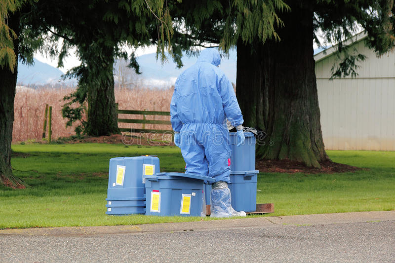 Avian Influenza Outbreak. A technician in full Hazmat suit prepares to enter a chicken barn to test for Avian Influenza stock photography