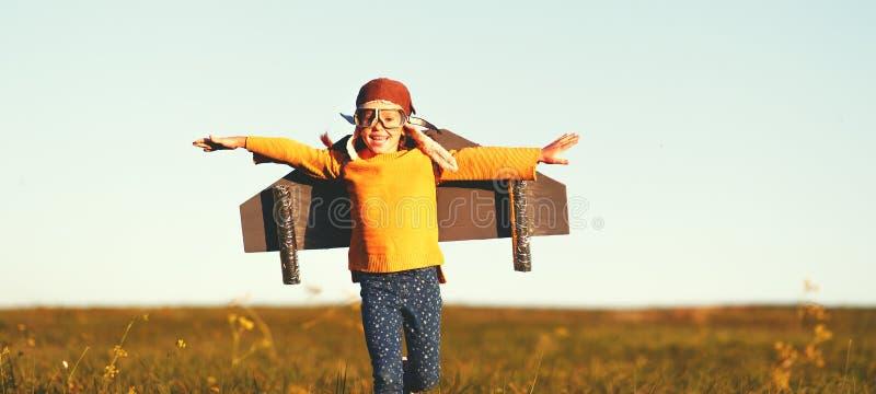 Aviateur pilote enfant avec des ailes d'avion rêve de voyager en été au coucher du soleil image libre de droits