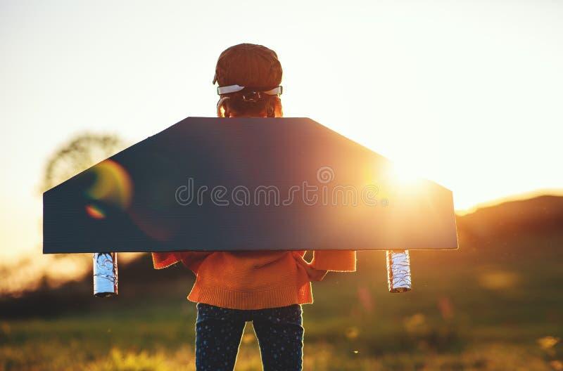 Aviateur pilote enfant avec des ailes d'avion rêve de voyager en été au coucher du soleil image stock
