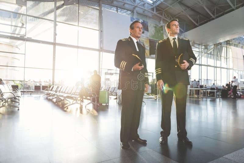 Aviateurs sérieux plaçant à l'aéroport images libres de droits