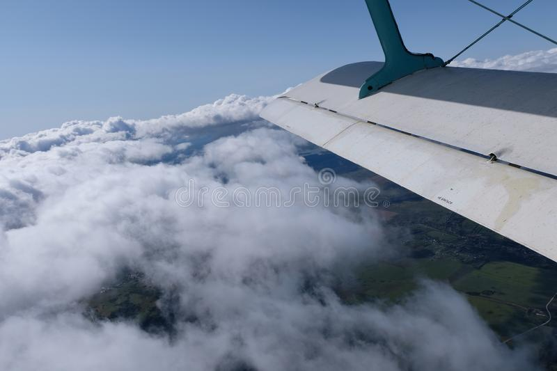 A view from airplane`s opened door. Aviation. An airplane is in the sky. The view from opened door.  A wing of the airplane and pretty clouds royalty free stock images