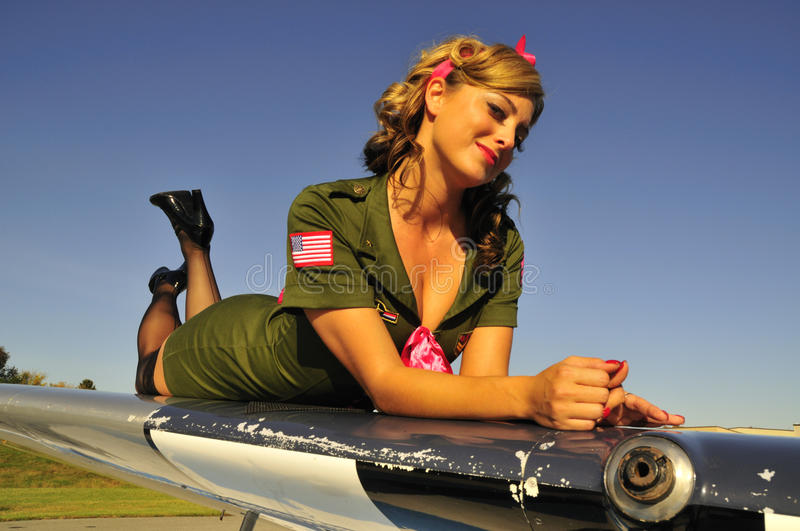 Aviation army girl. Army girl lying on an aircraft wing stock photo