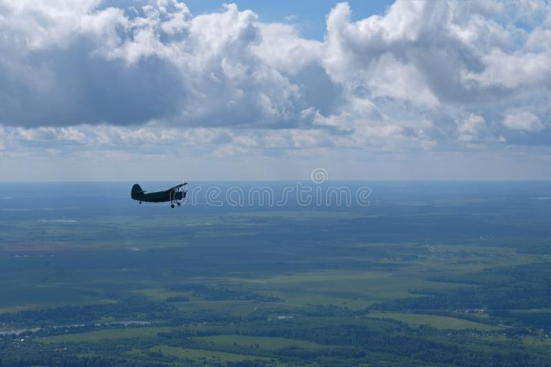 An old biplane is flying in the strong sky. royalty free stock image
