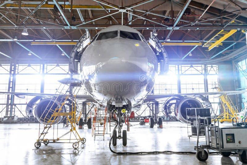 Aviation hangar with passenger aircraft jet for maintenance. Bright lights lighting, glare stock image