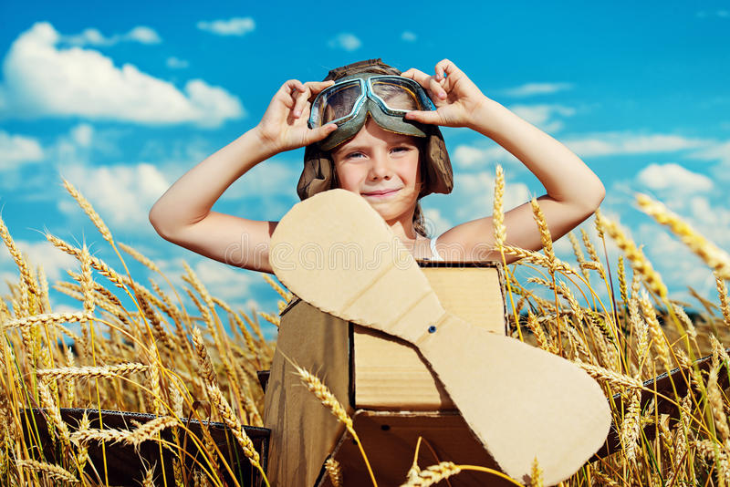 Aviation. Little dreamer girl playing with a cardboard airplane in the field over blue sky and white clouds. Childhood. Fantasy, imagination stock photo