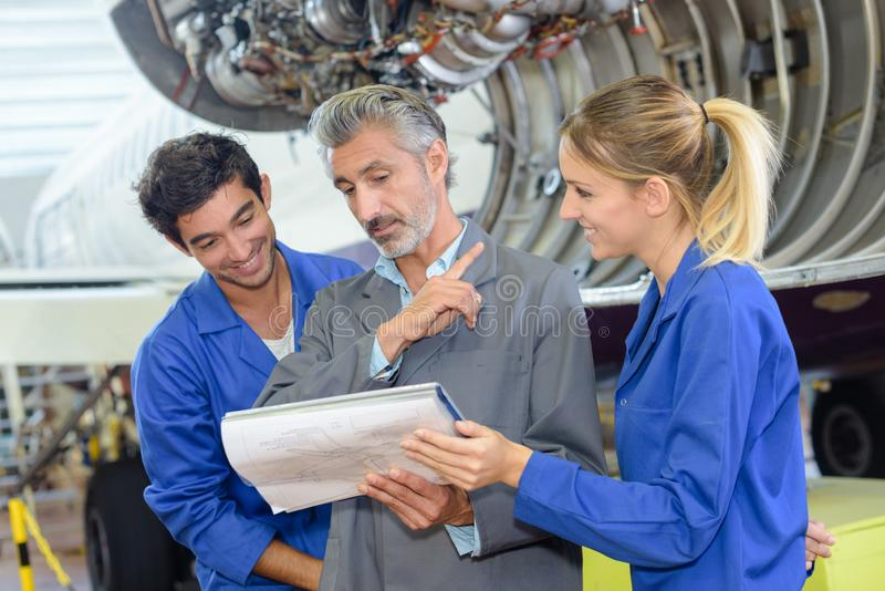 Aviation students looking at folder with teacher royalty free stock photography